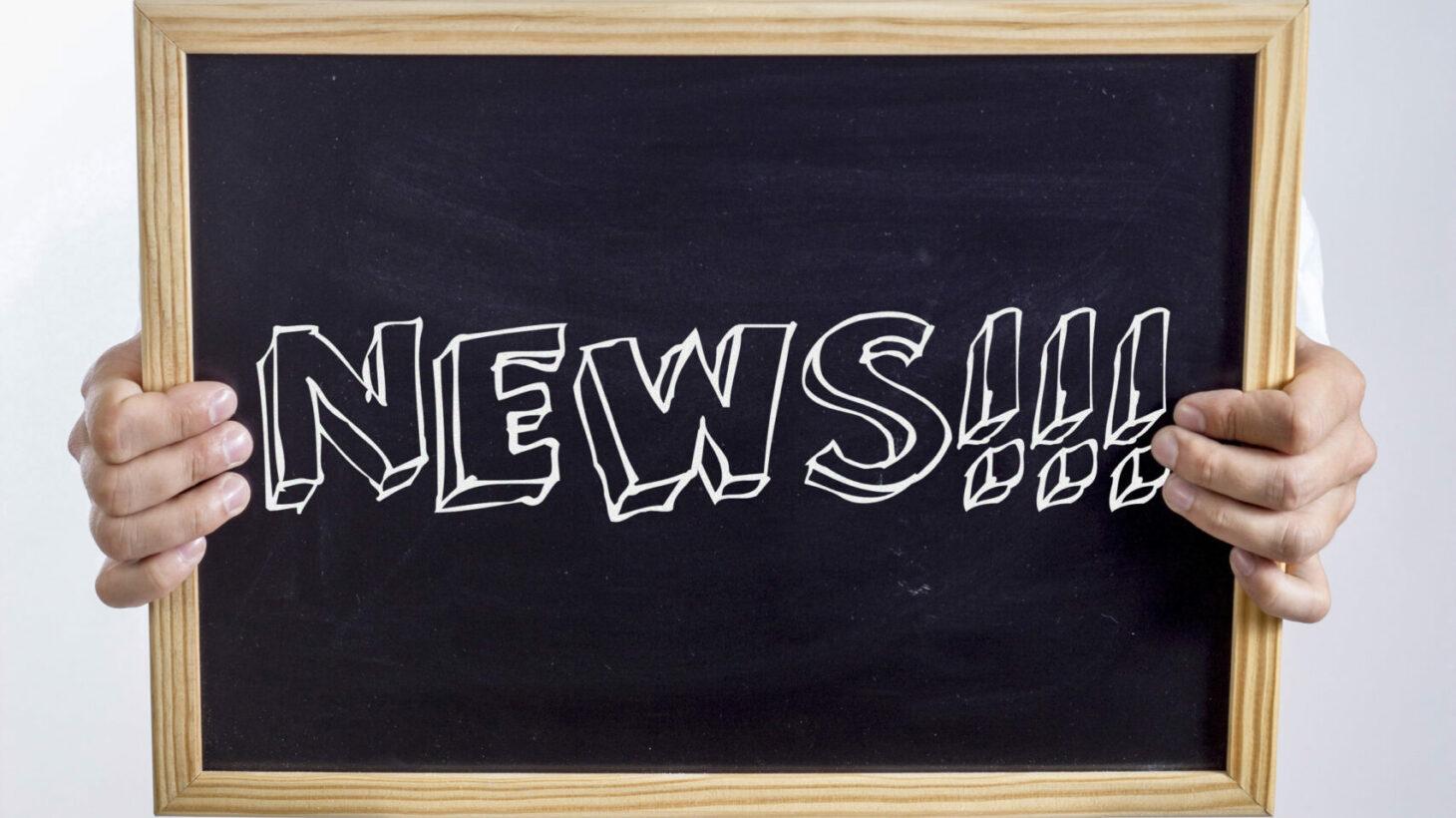 Händer håller i skylt med texten: News!