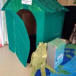 Ett grönt litet hus med en mjukdjurs-krokodil utanför.