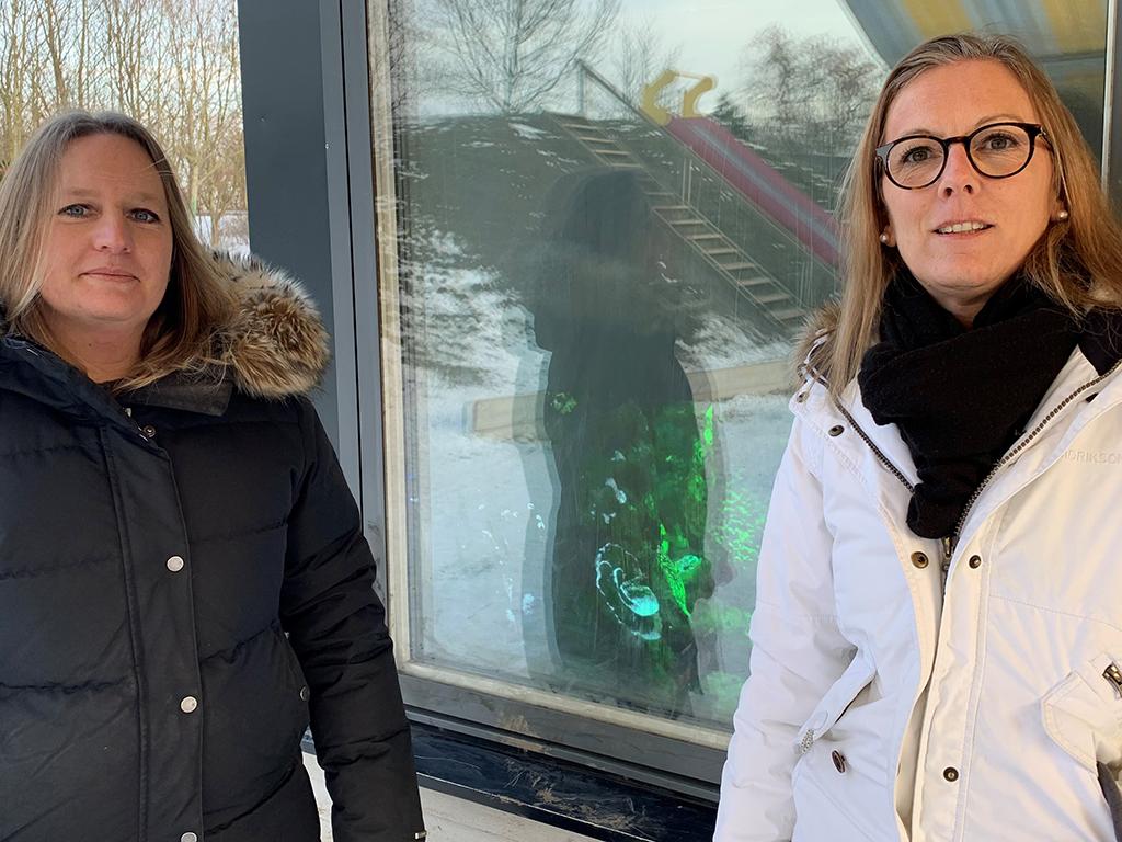 Linda och Linda står framför glasvägg.