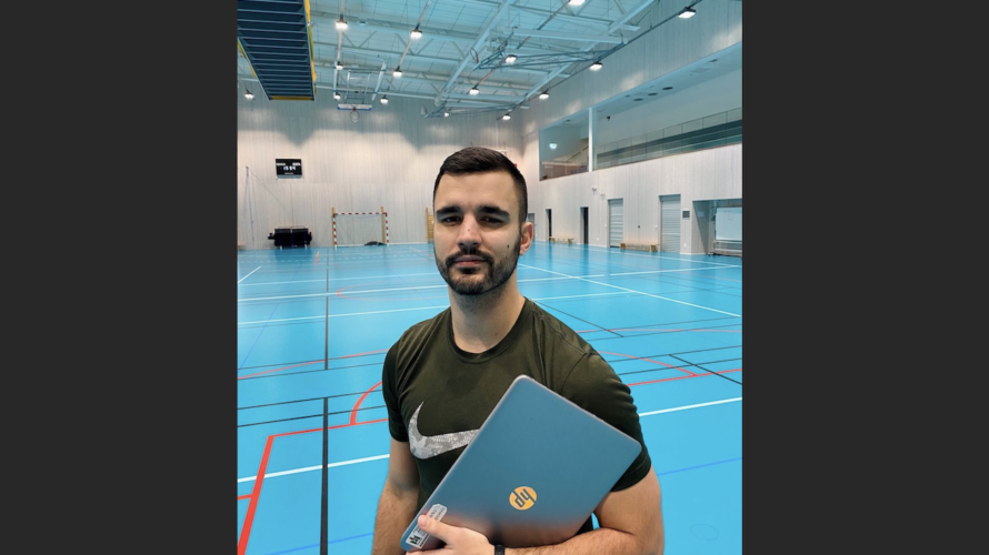 Marko Lapcevic håller i en dator i idrottshall.