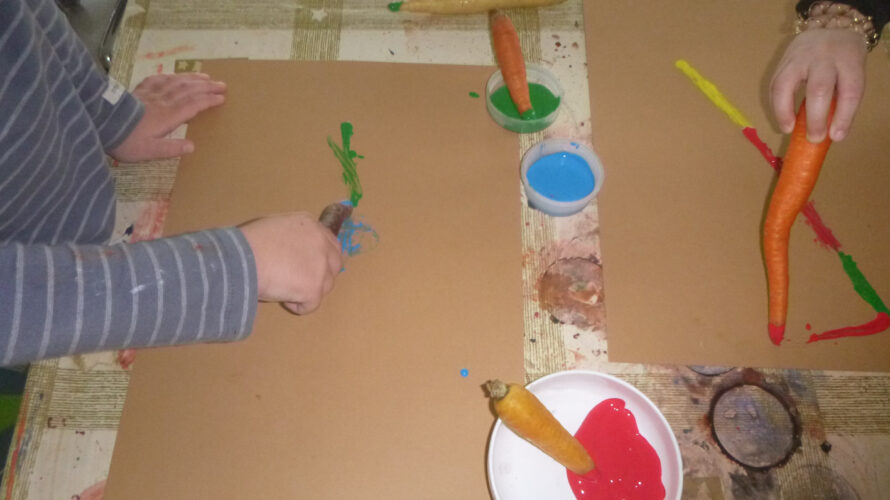 Barn målar med morötter som penslar.