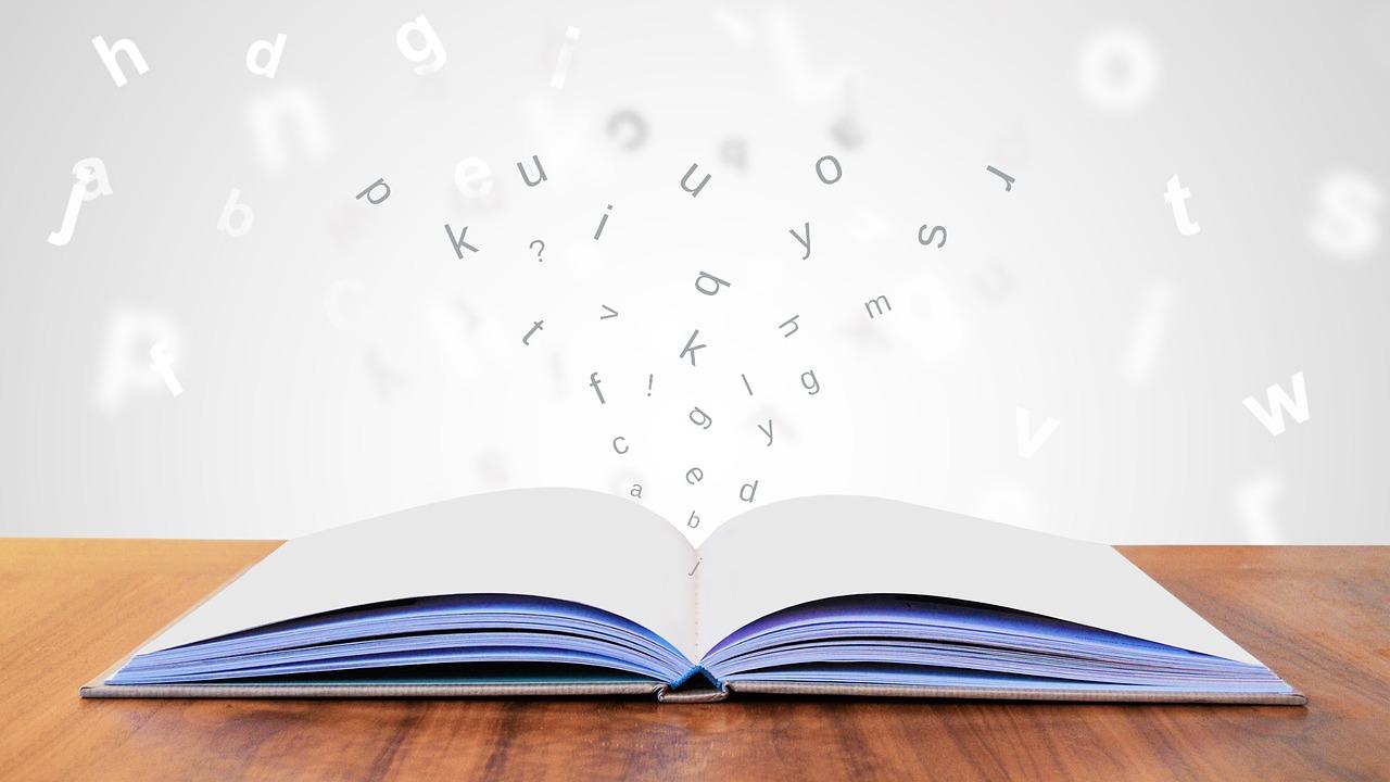 Uppslag bok med en svärm av bokstäver omkring.