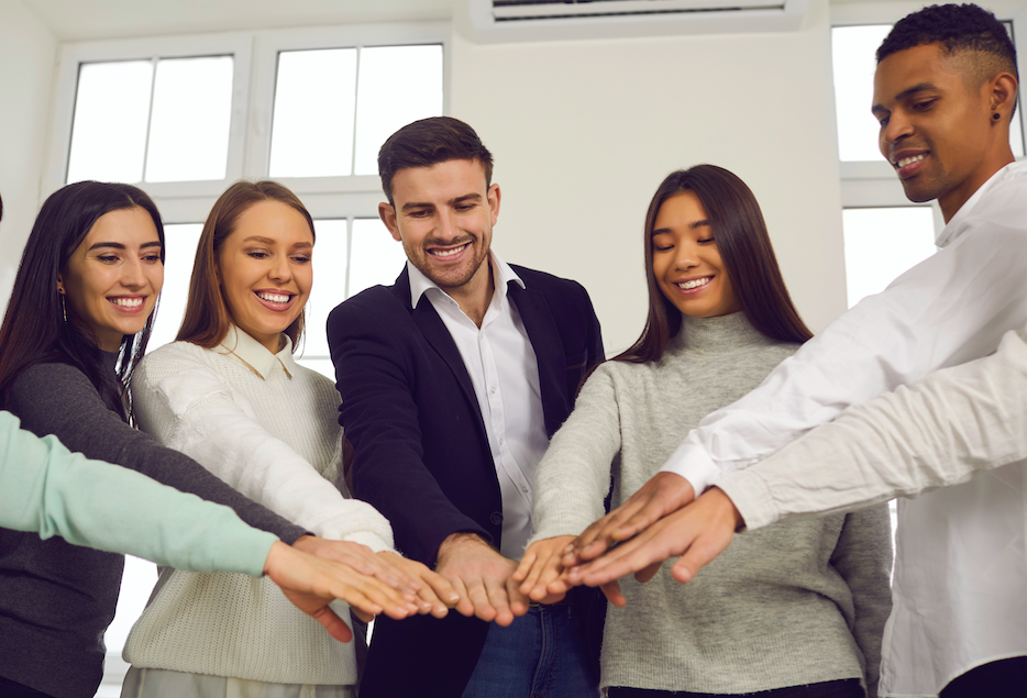 Fem ungdomar sträcker fram händerna.