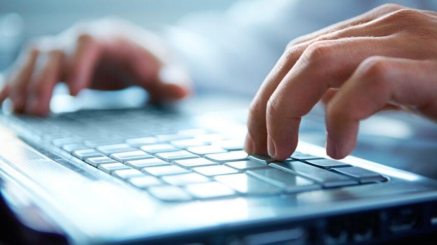 Närbild av händer som skriver på ett tangentbord.