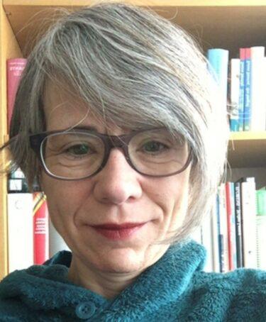 Kvinna i glasögon framför bokhylla.