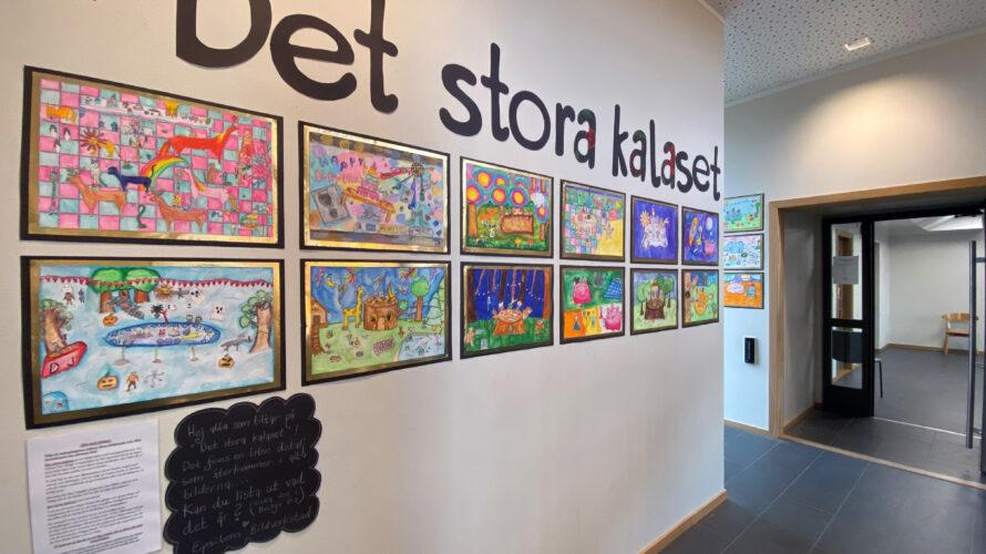 """Tavlor med färgglada målningar upphängda på en vägg. Det står """"Det stora kalaset"""" med stora bokstäver på väggen."""