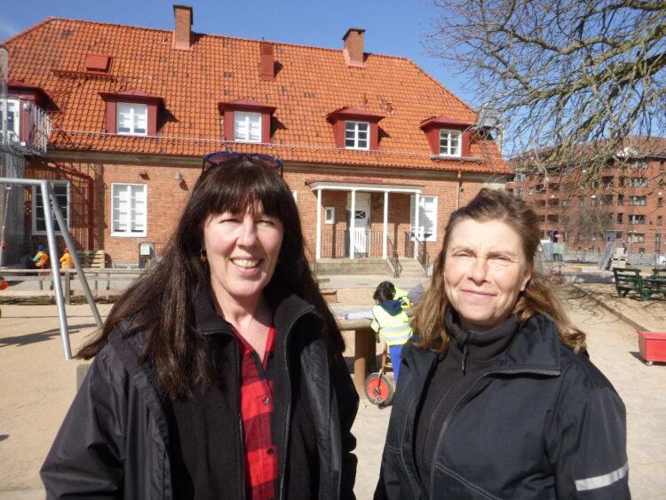Två kvinnor i strålande solsken på en förskolas gård.