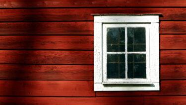 Litet fönster på röd trävägg.