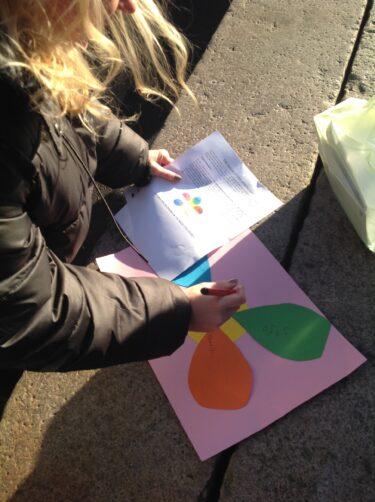 Barn håller i färgade papper.
