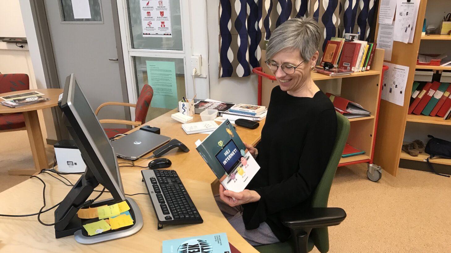 Jana Nylén sitter vid skrivbord i bibliotek.