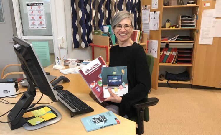 Jana Nylén sitter vid skrivbord i bibliotek och håller i böcker.
