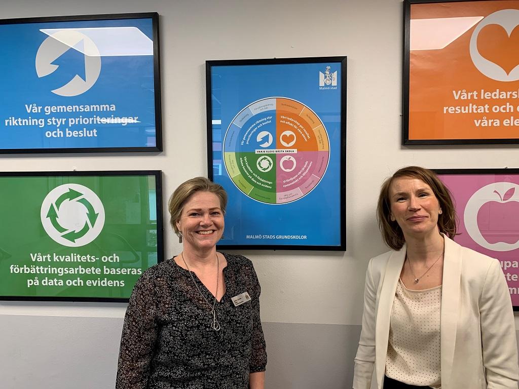 Två kvinnor står framför tavlor i olika färger.