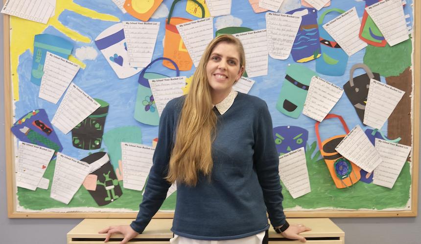 Marie Nilsson står framför elevarbeten i klassrum.