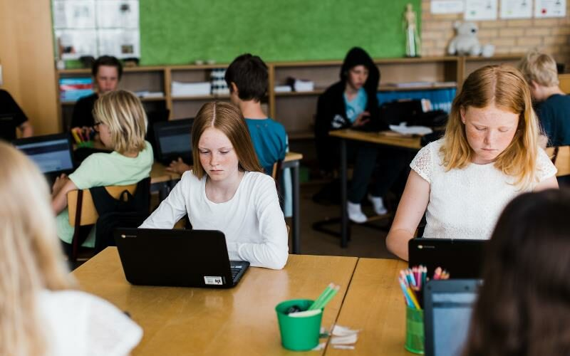 Elever sitter med datorer i skolbänk.
