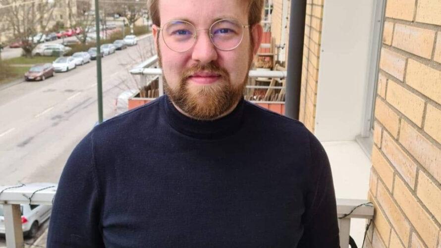 Porträttfoto på Pontus Källström ståendes på en balkong intill en väg.