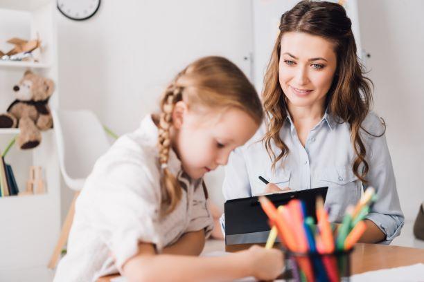Ett barn och en vuxen vid ett bord målandes och skrivandes.