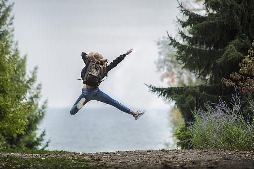 En person med ryggsäck på ryggen hoppar högt ute i skogen.