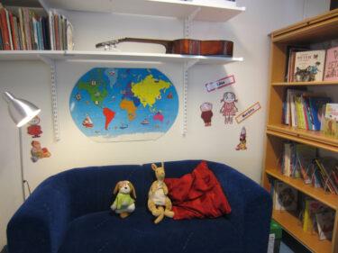 En soffa med gosedjur och hyllor fulla med böcker. Uppe på en hylla ligger en gitarr.