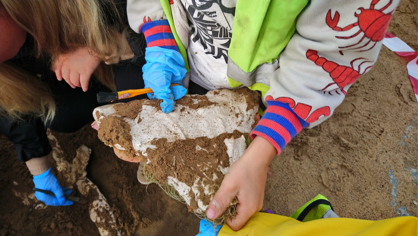 Barn håller i en cementbit med sand på.