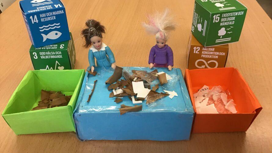 FN:s globala mål på pappboxar och två dockor.