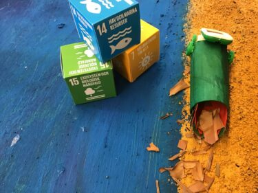 FN:s globala mål skrivna på pappboxar.