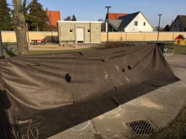 Ett stort svart skynke med hål i uppställt på en gård.