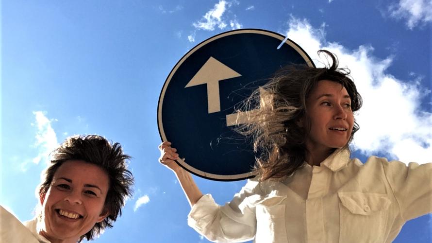Karin Wiknertz och Elin Kattler med en blå trafikskylt.