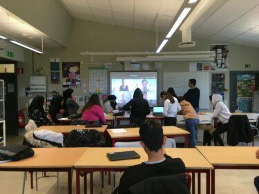 Elever i klassrum deltar i videomöte.