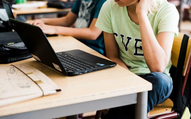 Kille sitter i skolbänk, framför bärbar dator.