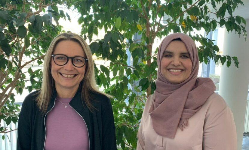 Två kvinnor med växter i bakgrunden.