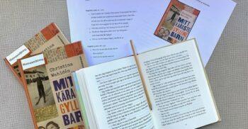 Uppslagen bok ligger bredvid andra böcker och utskrivna texter