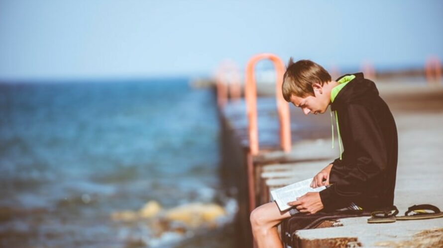 Kille sitter på brygga och läser.