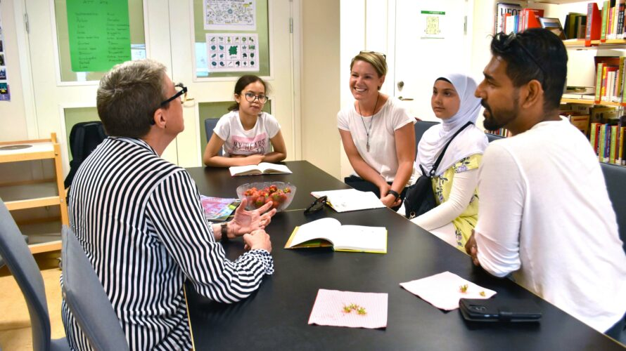 Elever och skolpersonal samtalar vid ett bord i skolbiblioteket.