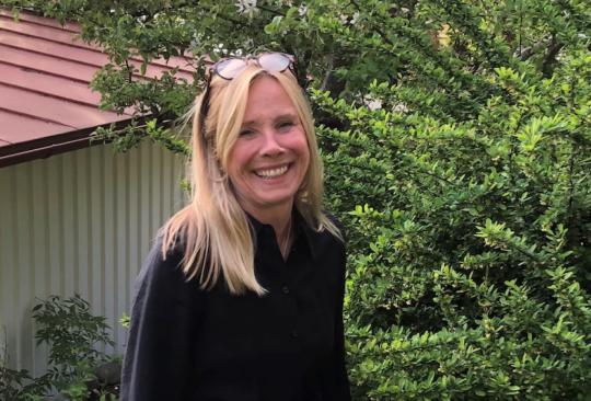 Anneli Schwartz står i grönskande trädgård.