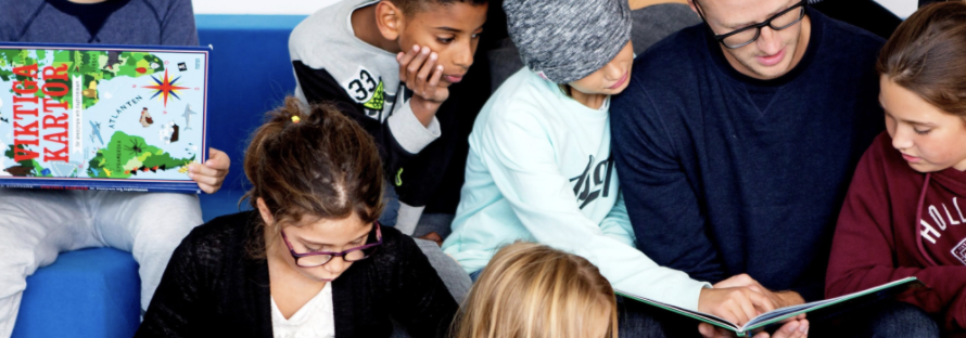Lärare och elever läser i en bok.