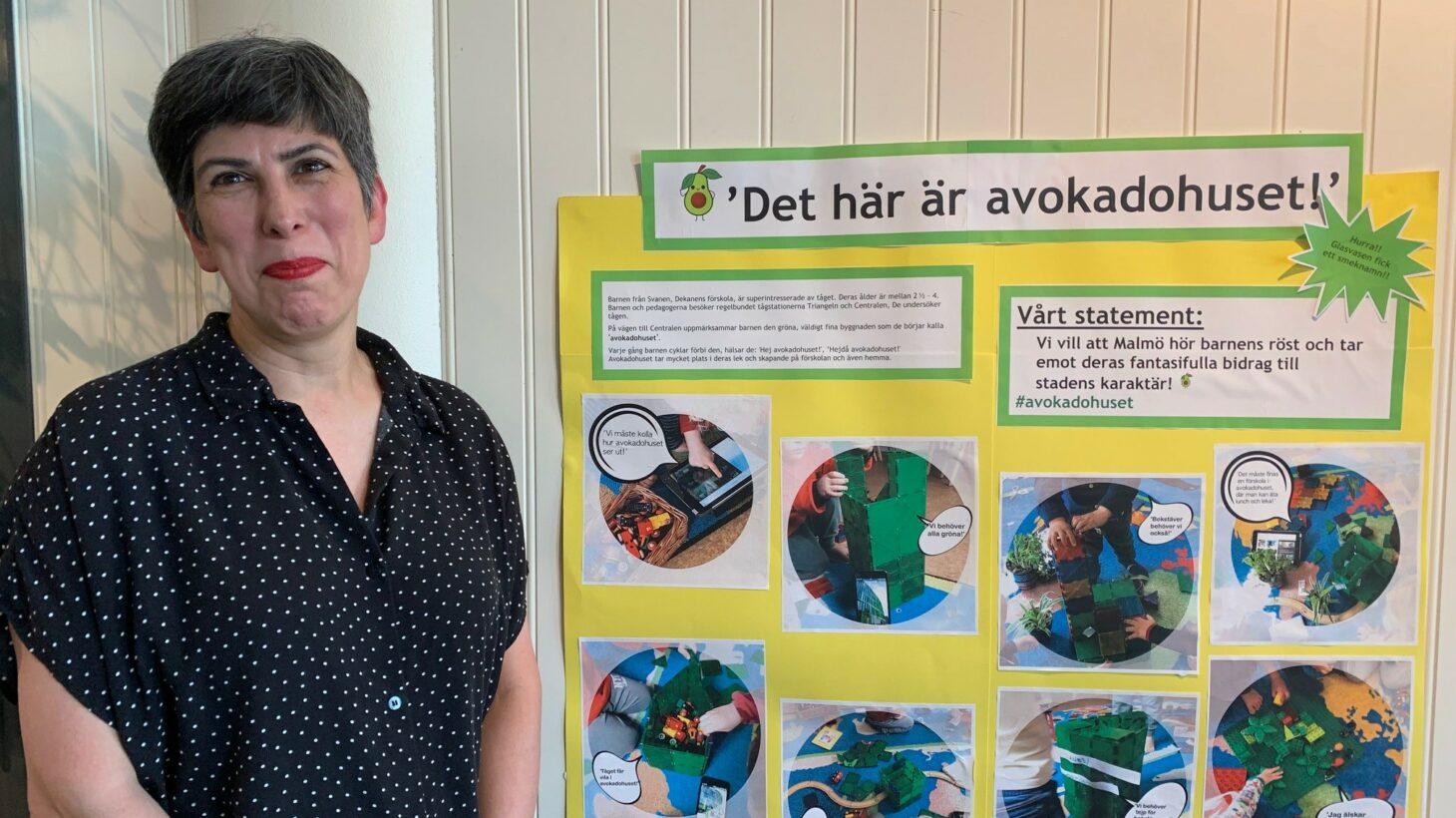 Dilek står framför en poster med information om arbetet med avokadohuset.