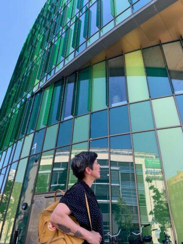 Dilek står framför en byggnad med glasväggar i olika gröna nyanser.