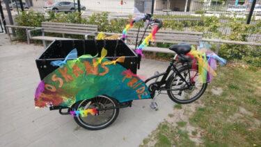 Lådcykel utsmyckad med regnbågsfärger.