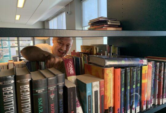 Fredrik Lindskoug sorterar böcker.