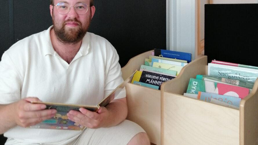 jag vid en bokhylla hållandes i en bok