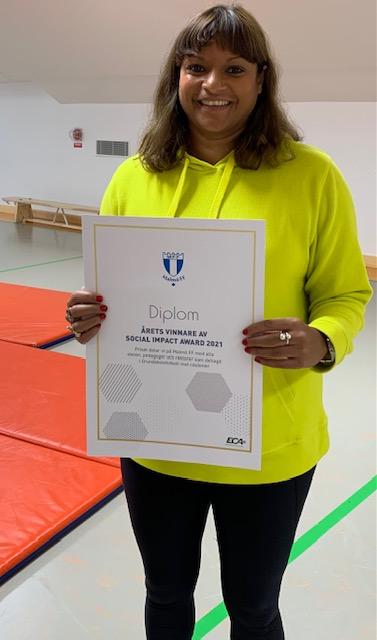Miriam Fairbairn håller upp ett diplom.