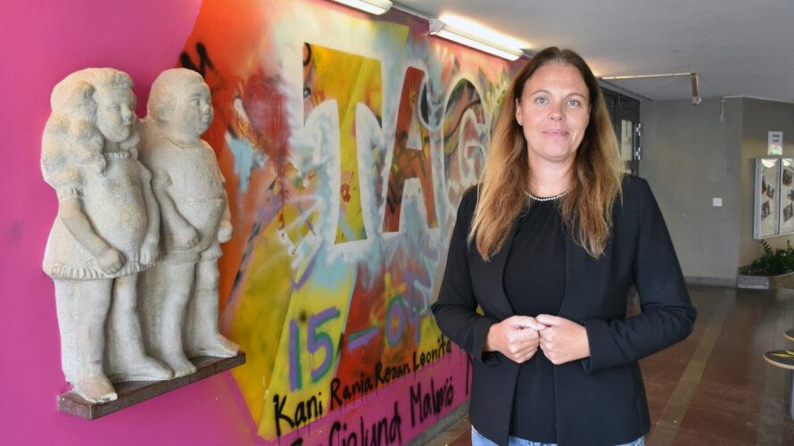 Malin Pantzar står framför en målad vägg och statyer på Sofielundsskolan.