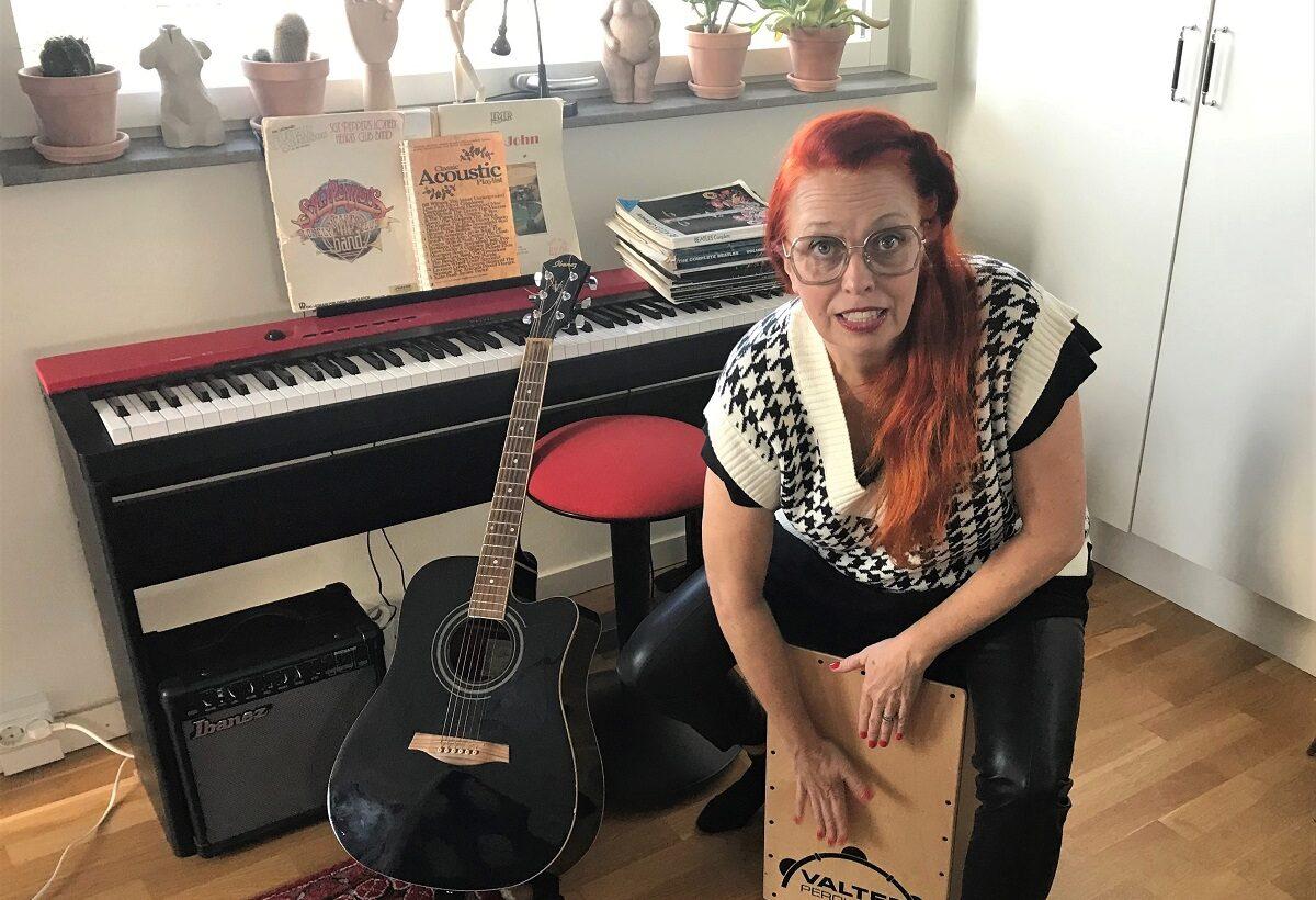 Camilla Jonasson framför ett piano och ett gitarr. Hon spelar cajón.