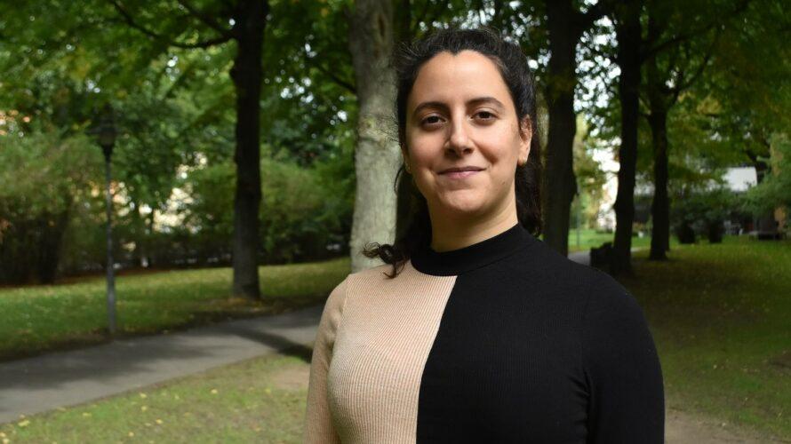 Dahlia Naji står utomhus vid några träd.